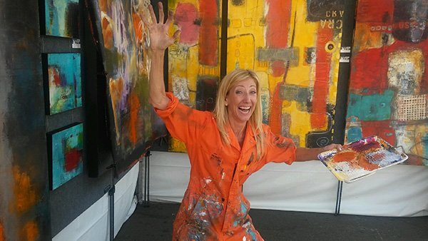 image of ann golumbuk in front of a few of her abstract paintings that will be shown at art walk little italy