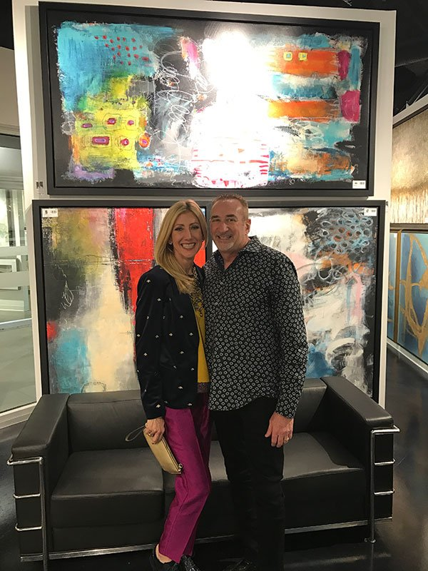 ann golumbuk and husband jeff golumbuk in front of ann's abstract style painting at the leftbank art gallery event